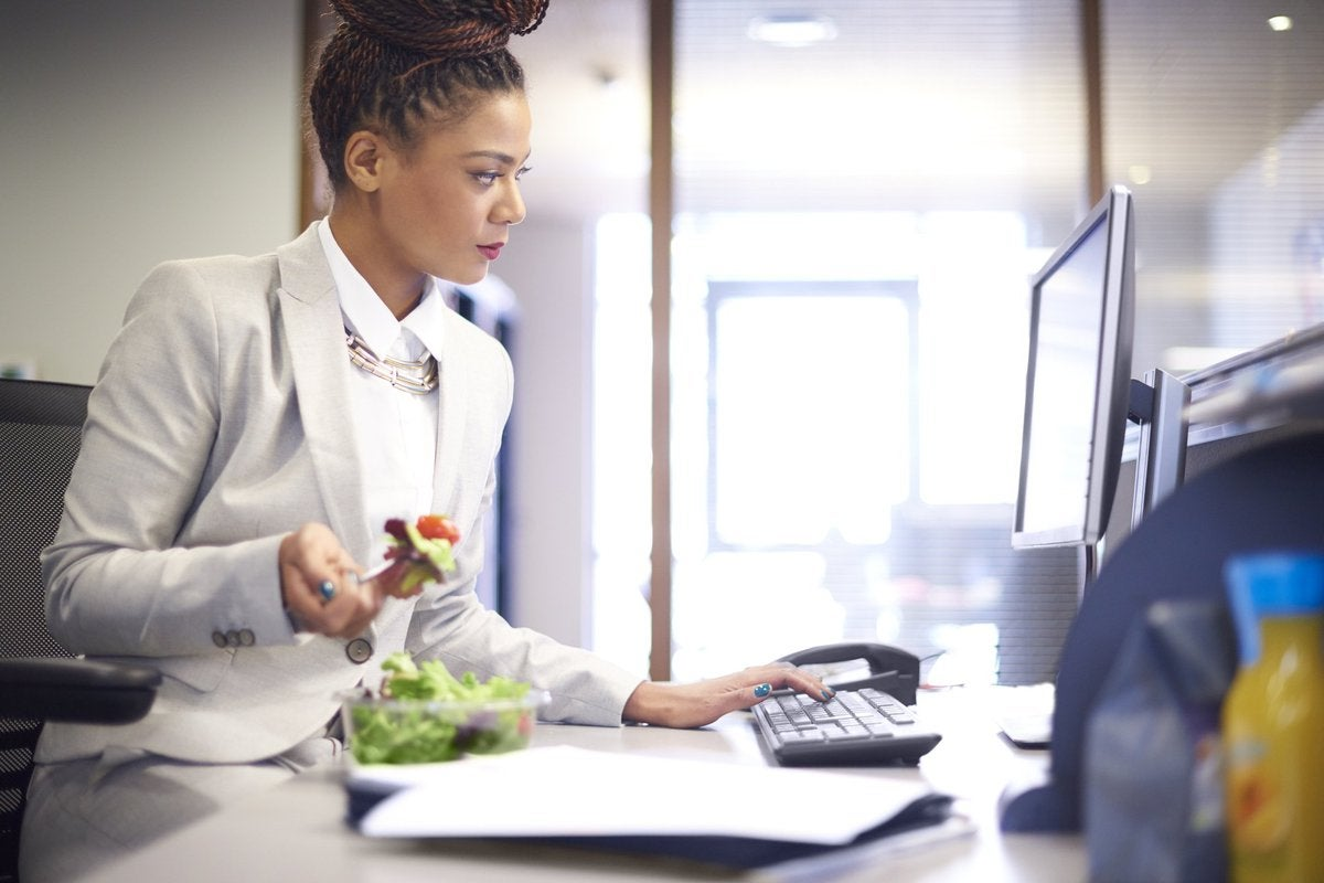 A young businesswoman eating a salad at her desk at work.