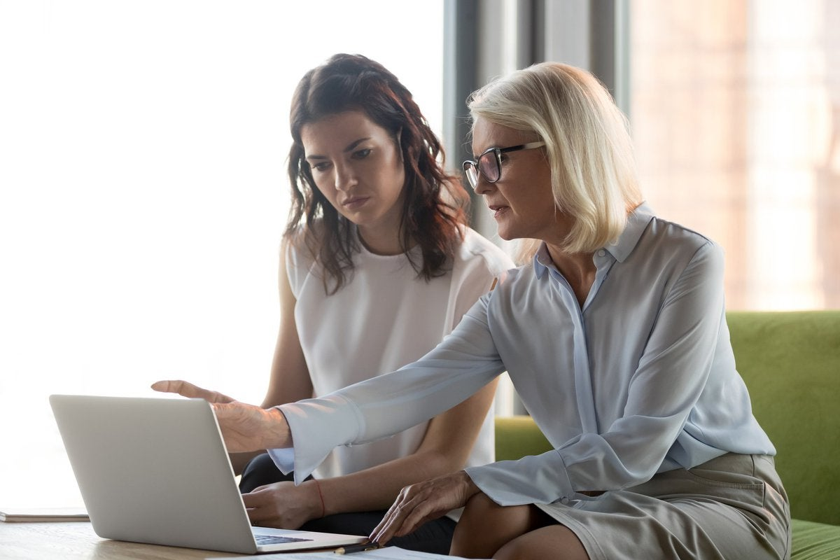 A financial advisor and her female client sitting together on a couch and looking at a laptop.
