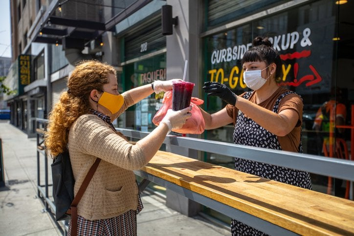 A woman being handed her takeout order from an employee outside a restaurant.