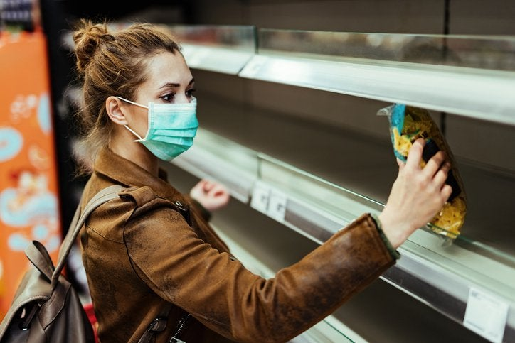 A woman wearing a medical mask and picking up the last bag of pasta from the grocery store shelf.