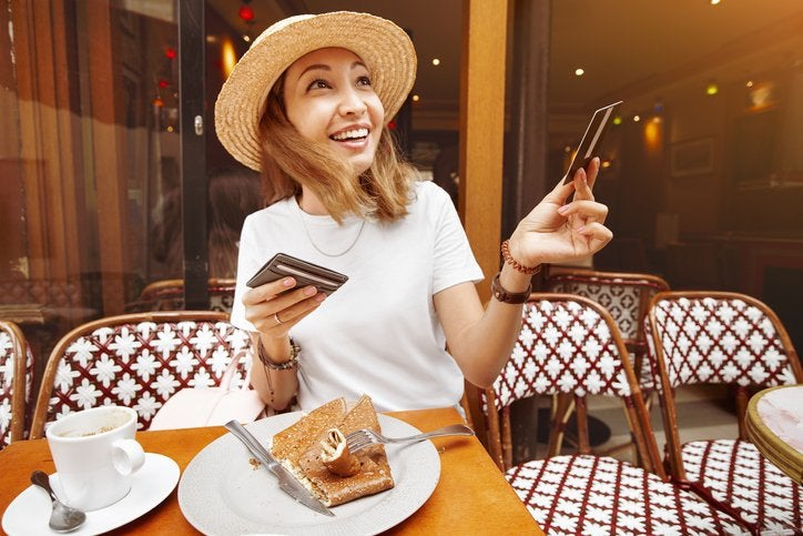 A smiling woman handing her credit card for payment while seated at an outdoor cafe table.