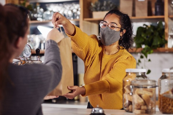 A woman wearing a medical mask and handing a bag of takeout food to a customer over a counter in a restaurant.