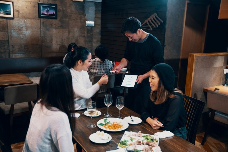 Three women dining at a restaurant while one hands her credit card to the waiter.