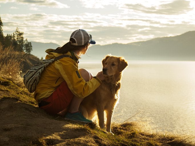 A woman hiking around a lake with her dog and taking in the view over the water at sunset.