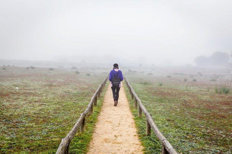 A woman hiking down a dirt path through a foggy field
