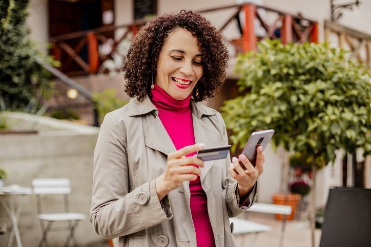 A smiling woman standing outside a sidewalk cafe looking at her phone while holding a credit card.