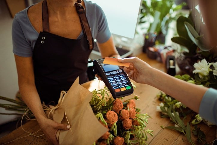 A woman tapping her credit card on a payment reader being held out by a florist in a flower shop.