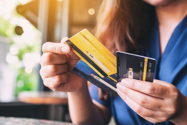 A woman holding several credit cards and pulling one out above the others.