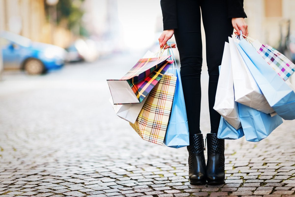 A woman holding a lot of shopping bags.