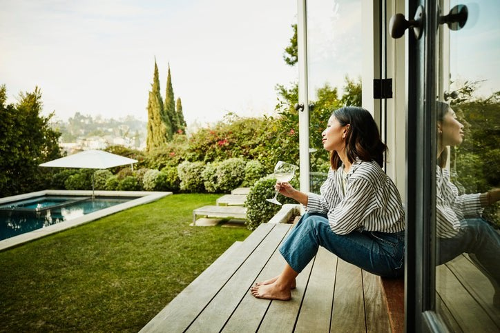 A smiling woman holding a glass of wine while seated on the steps of a patio deck looking at her backyard.