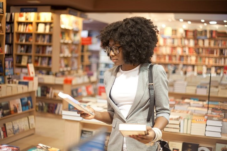 A woman holding a book in each hand while browsing in a bookstore.