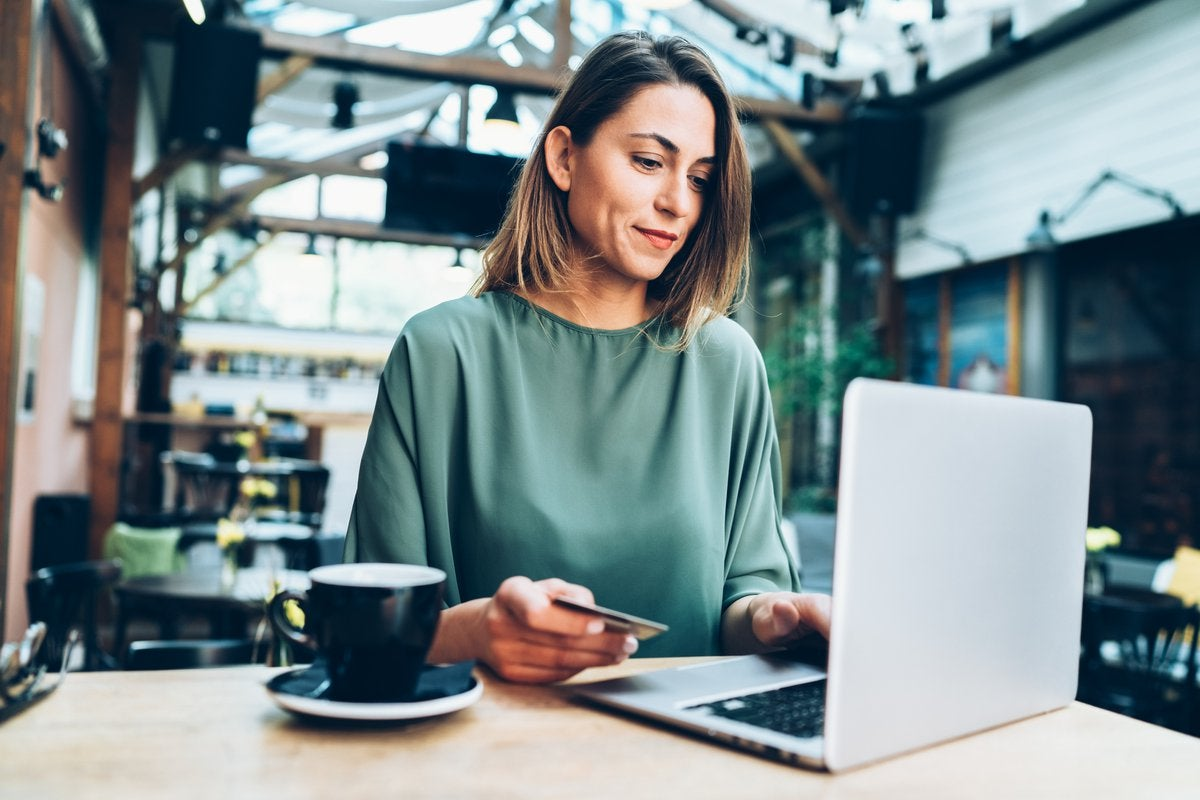A woman in a cafe sitting at a table with her laptop and holding a credit card.