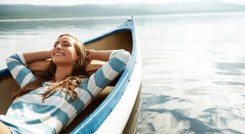 A smiling woman laying back in a canoe on a lake on a sunny day.