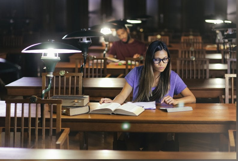 A female college student studying in an almost-empty library.