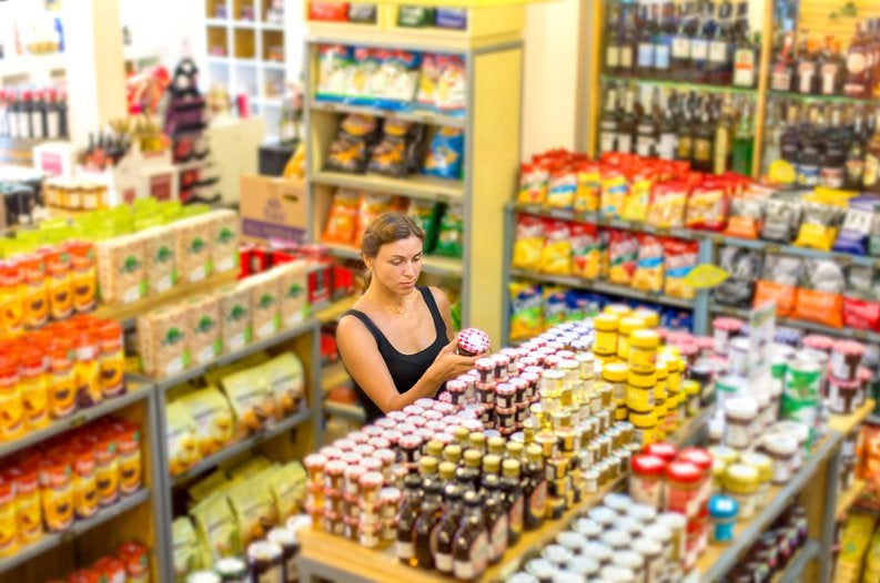 A woman looking at jars of food in an empty grocery store.