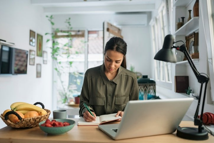 A woman sitting at her kitchen counter next to bowls of fruit and a laptop and writing in a notebook.