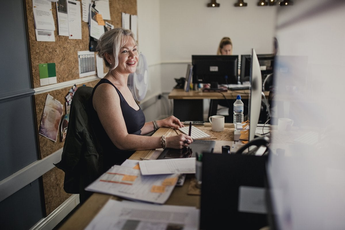 A smiling woman working at her desk in an office.