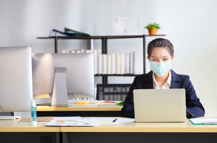 A woman wearing a medical mask while working at a computer in an office.