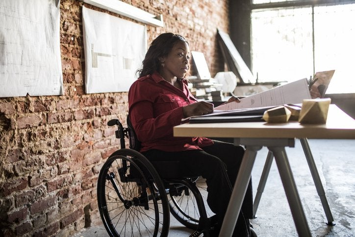 A woman in a wheelchair looking through large documents on a table with more hanging on the brick wall behind her.