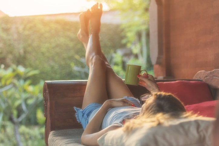 A woman lying down on a patio chair, looking at her sunny backyard, and holding a coffee mug.