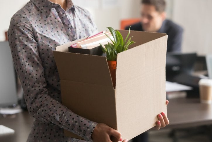 A woman who has just been let go from her job leaving the office with a box of her things.