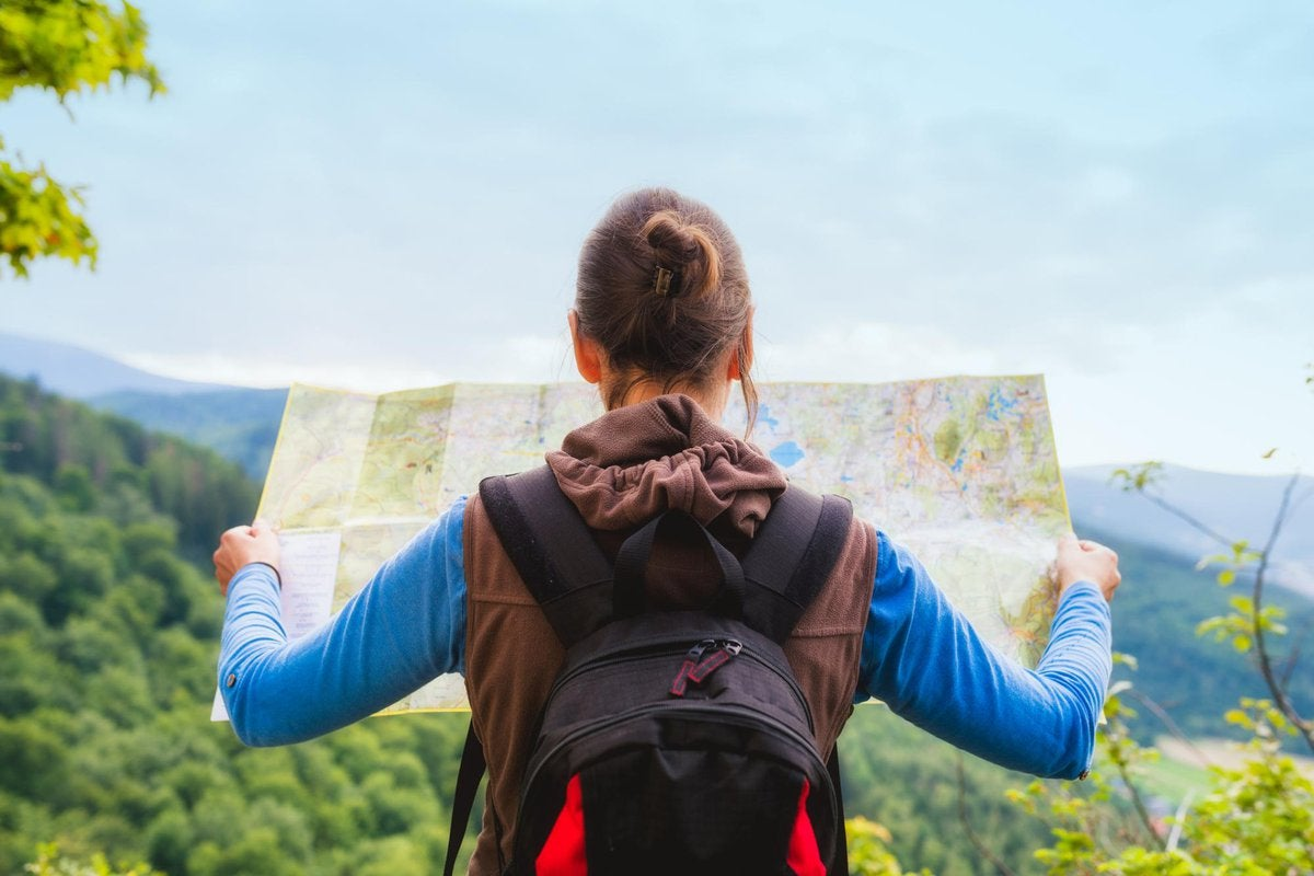 woman looking at map while hiking in nature