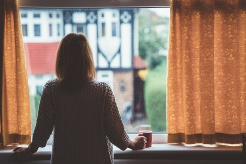 A woman standing at the window in her home and looking out at the neighborhood.