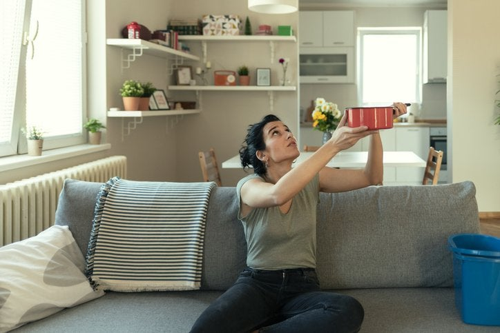 A woman sitting on her couch and holding up a pot to catch a leak falling from the ceiling.
