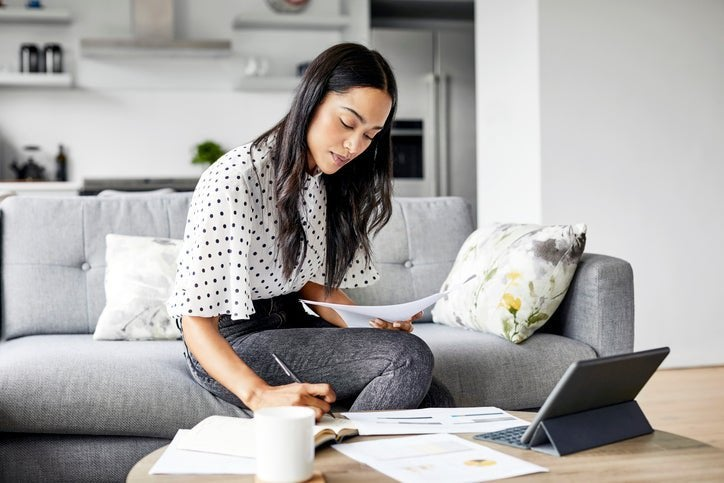 A woman sitting on her couch and looking over paperwork with a tablet open on the coffee table.
