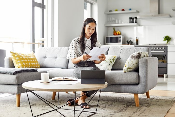 A woman sitting on the couch in her living room reading paperwork in her hand.