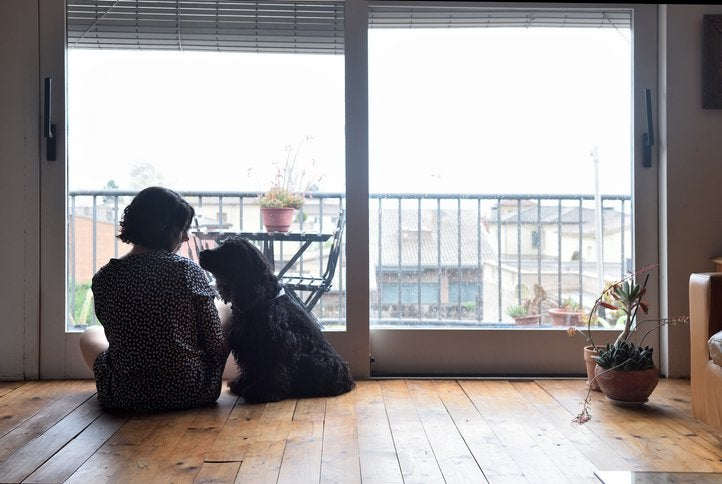 A worried woman sitting on the floor with her dog in front of her living room balcony window.