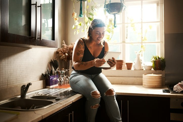 A woman sitting on the kitchen counter in her apartment and smiling at a tablet she's holding.