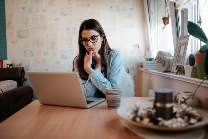 A worried-looking woman looking something up on her laptop while sitting at her kitchen table.
