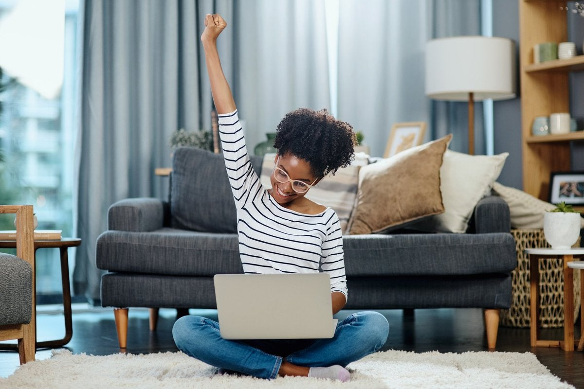 A woman sitting in front of her couch with her laptop and celebrating with her hand in the air.