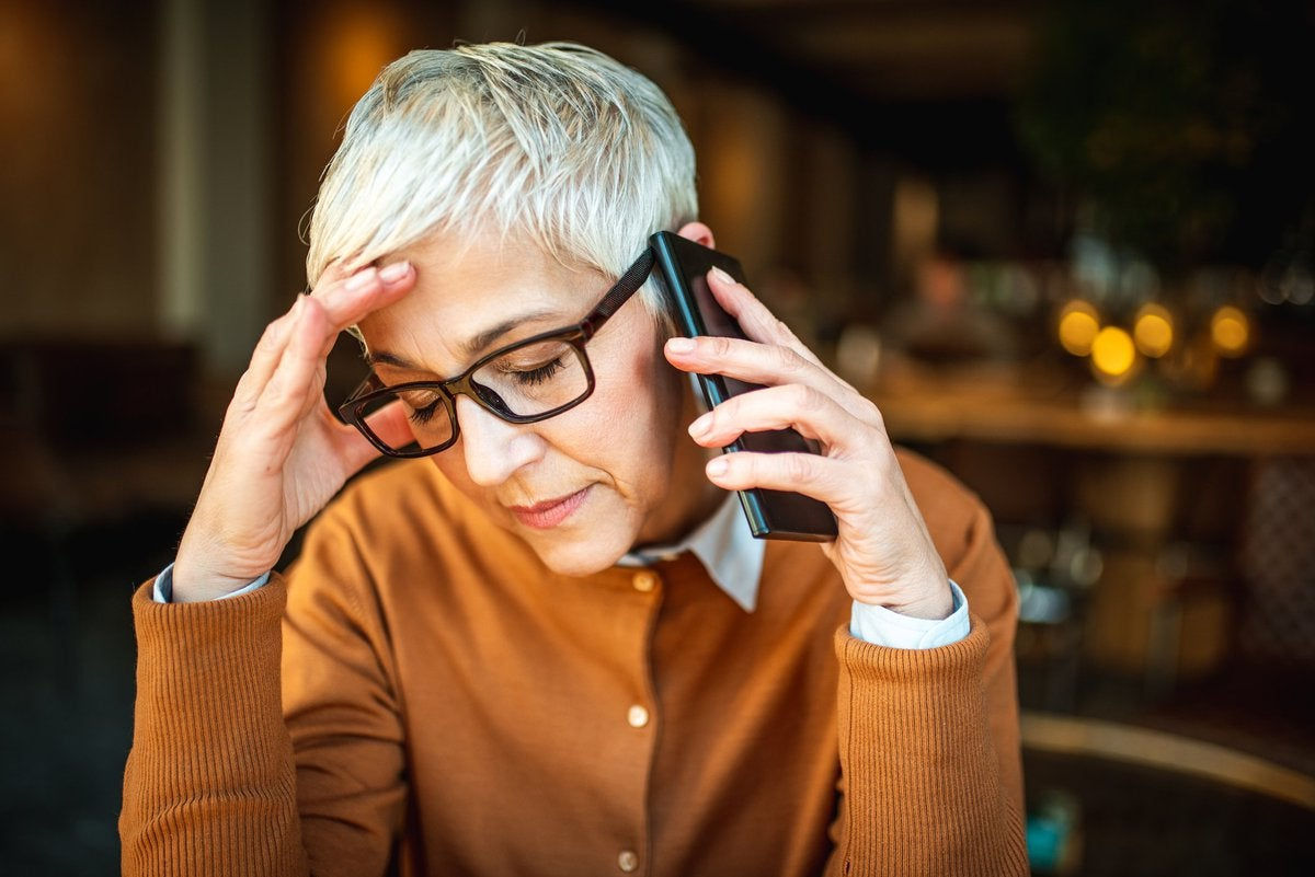 A woman on a phone call with her hand on her forehead seemingly getting bad news.