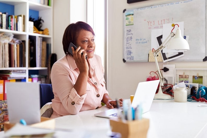 A woman on a phone call while sitting at her desk in her office.