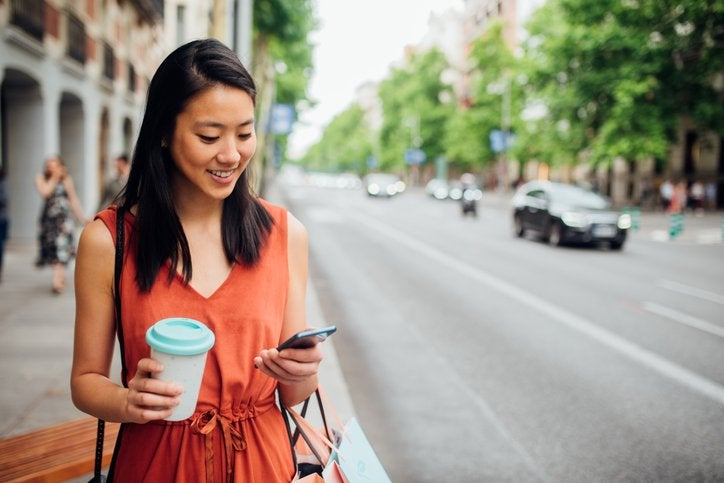 A young woman walking down the street with a coffee in one hand and looking at her phone in her other hand.