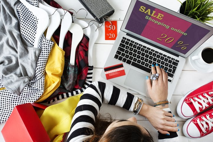 A woman shopping an online sale from her laptop while surrounded by clothes and shoes.