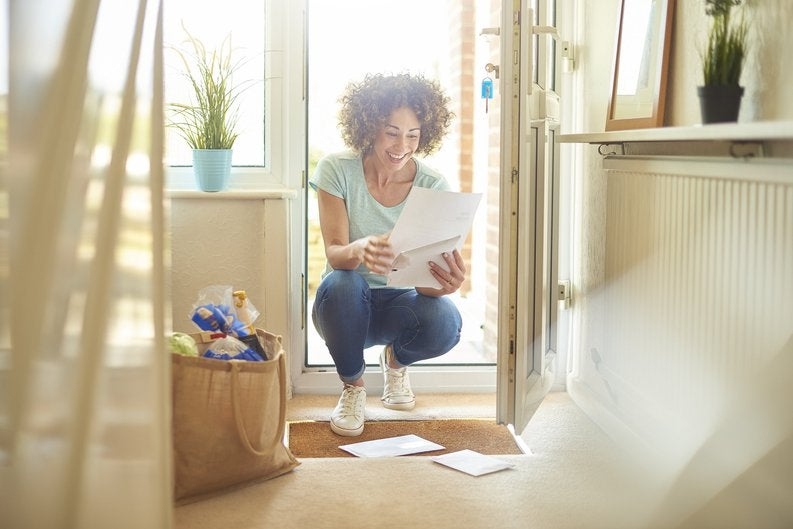 A woman smiling while opening mail in her sunny entryway.