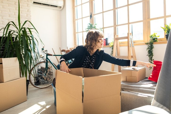 A young woman packing moving boxes in the living room of her sunny apartment.