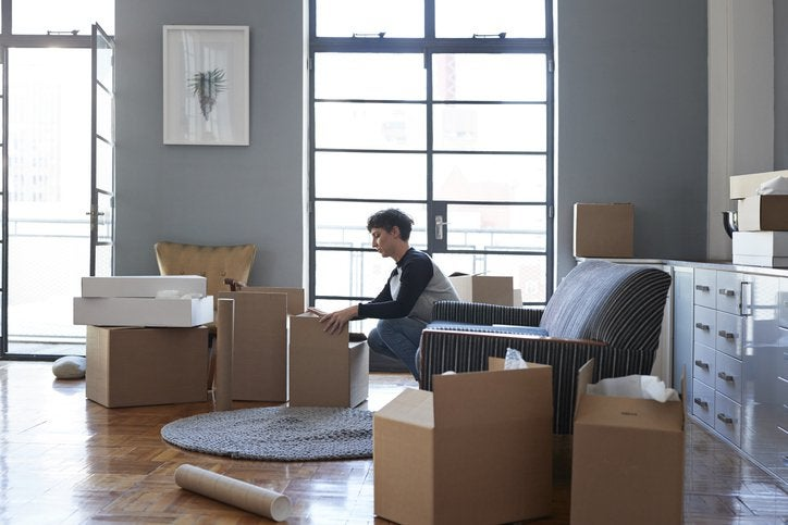 A woman packing moving boxes in her living room.