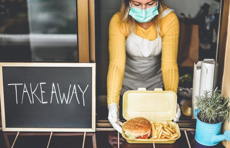 A woman wearing a medical mask handing a burger and fries through a window next to a sign that says Takeaway.