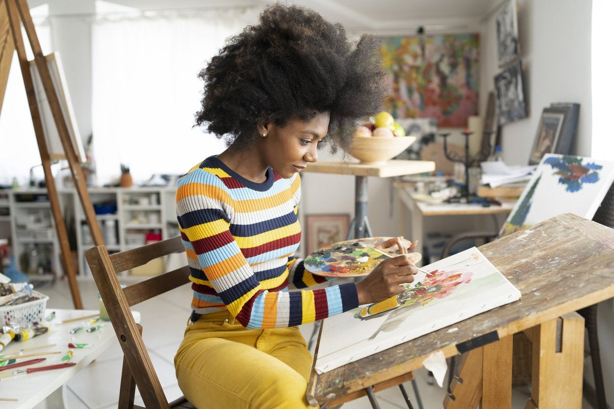 A woman painting in her home art studio.