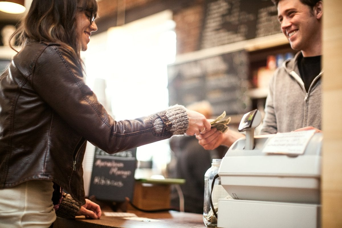 A woman handing money to a cashier at a coffee shop.
