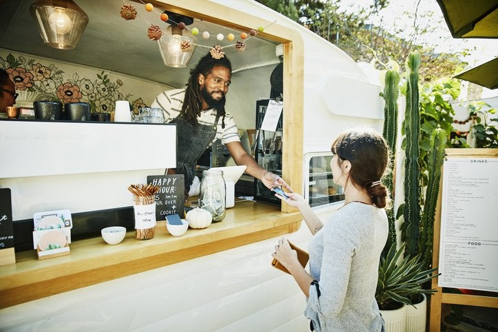 A woman handing her credit card through the window of a food truck to the owner standing inside wearing an apron.