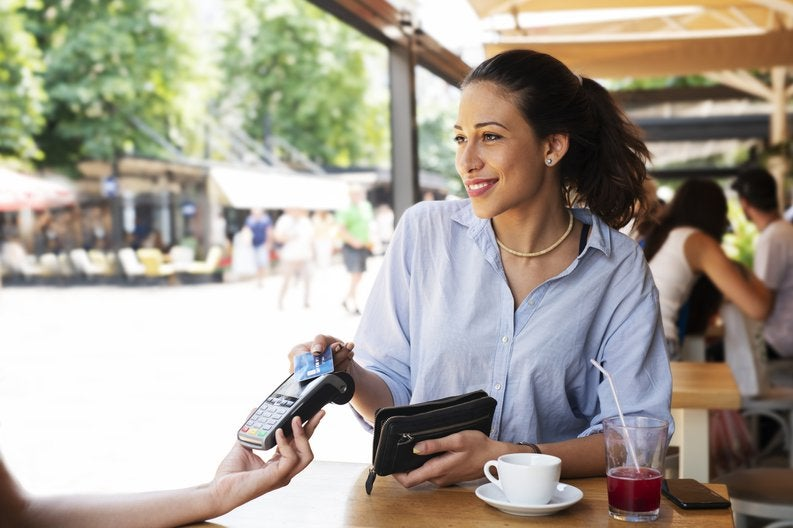 A woman sitting at a patio table and paying a waitress with her credit card.