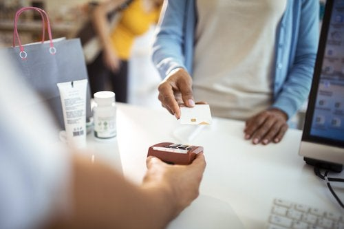 A woman holding her credit card up to the payment reader at the pharmacy.