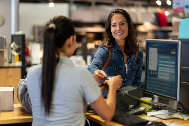 A woman handing her credit card to the employee at a cashier stand in a department store.