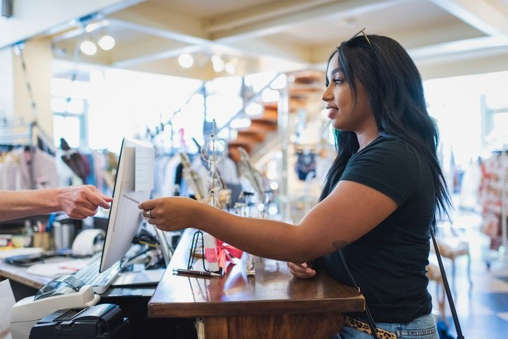 A woman handing her credit card to the cashier behind the counter in a clothing store.
