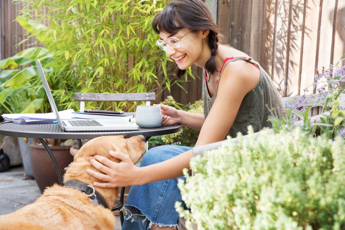 A person petting a dog while sitting outside at a patio table with an open laptop and a cup of coffee.